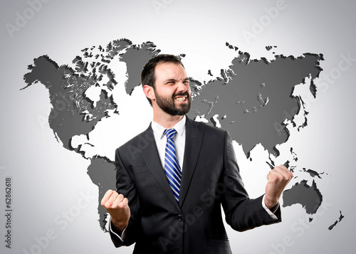 Young business man winner over world map background