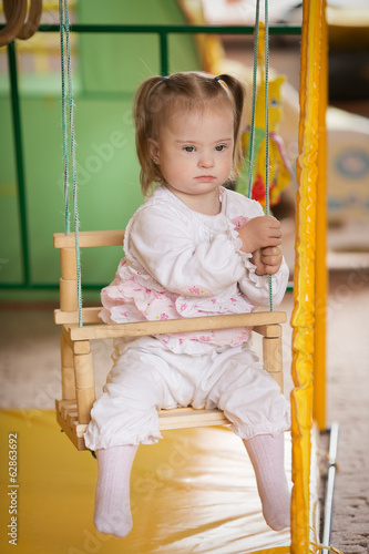 Girl with Down syndrome is riding on a swing