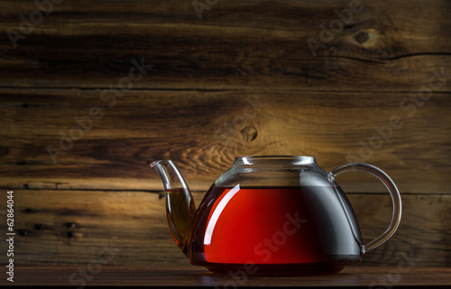 Fotobehang Thee glass teapot on a wooden background