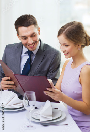 smiling couple with menu at restaurant