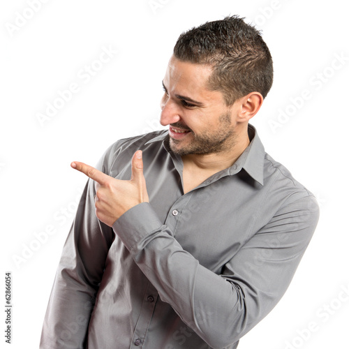 Young man pointing over white background