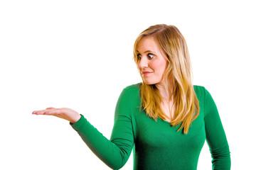verdutzt schauende Frau präsentiert etwas