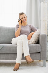 Happy young woman sitting on divan and talking cell phone