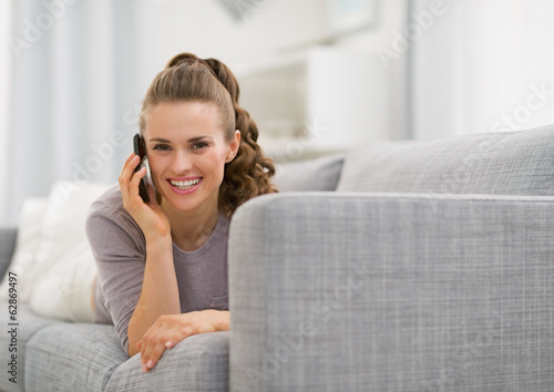 Smiling young woman laying on sofa and talking cell phone