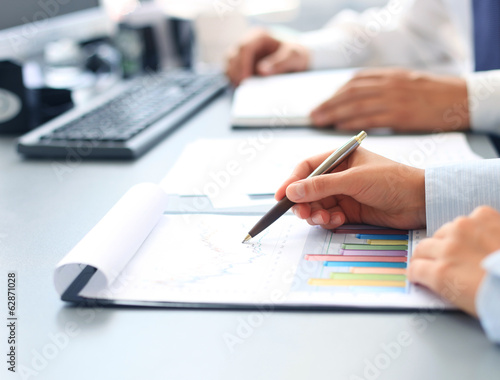 Unrecognizable business person analyzing graphs