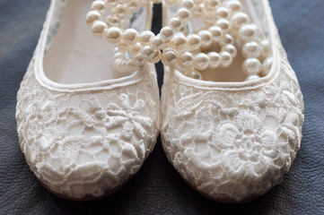 White bridal shoes with pearl bracelet