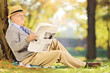 Smiling senior gentleman on grass reading a newspaper in park at