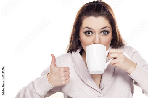 beautiful woman drinking from a cup and showing thumbs up
