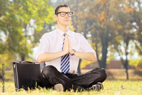 Businessperson with eyeglasses doing yoga exercise in park