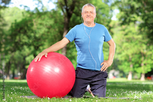 Mature man with an exercise ball in park