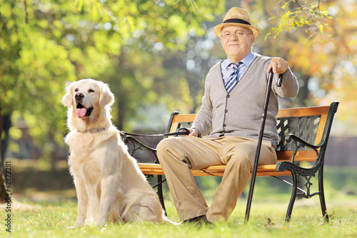Senior man seated on a wooden bench with his dog relaxing in par