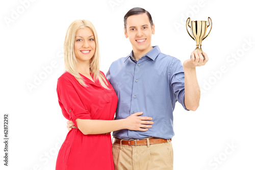 Young couple holding a gold cup