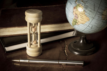 Hourglass and globe with stationary.