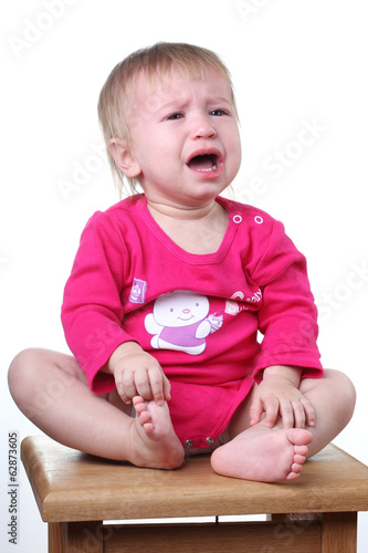 crying small child sitting on a stool