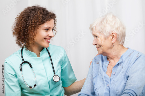 Smiling nurse and happy elderly lady