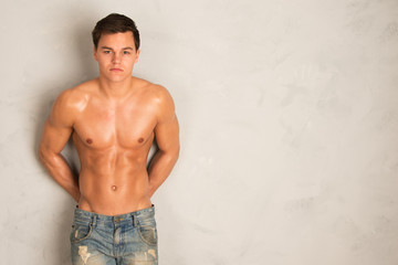 young fit man leaning against a wall