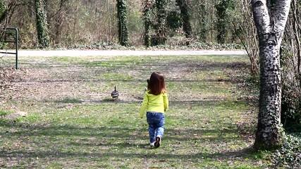 bambina che rincorre due anatre