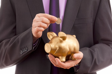 Business man putting coin into piggy