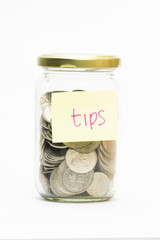 Isolated coins in jar with tips label - financial or business co
