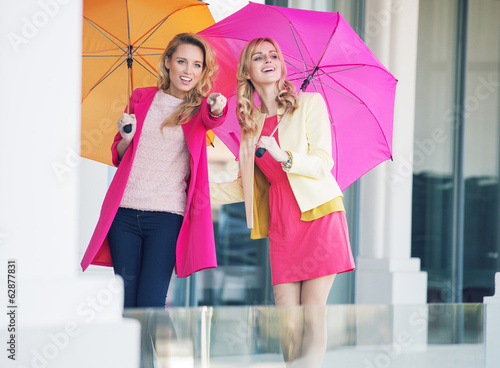 Attractive girlfriends with the colorful umbrellas