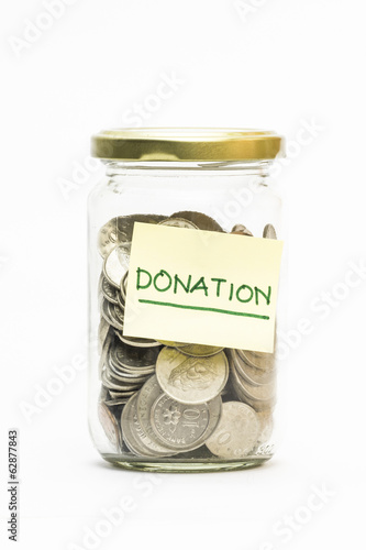 Isolated coins in jar with donation label