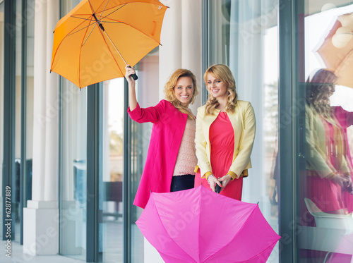 Cheerful ladies posing with the umbrellas