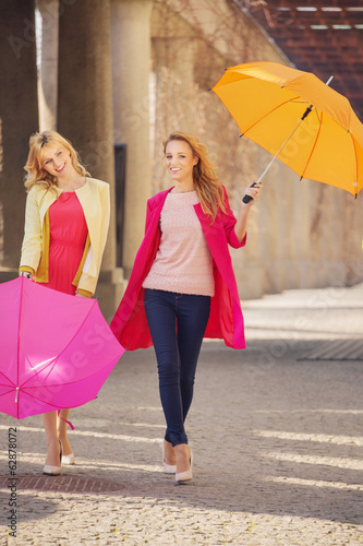 Two attractive girlfreinds with the umbrellas