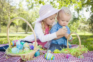 Cute Young Brother and Sister Enjoying Their Easter Eggs Outside