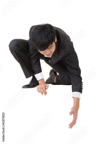 Asian businessman sit and bend down to help somebody