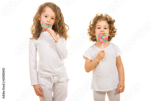Two girls eating lollipops