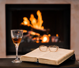 glass of cognac and book by the fireplace