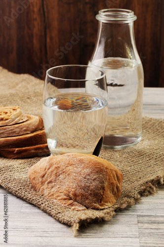 Water in a bottle and a glass and bread