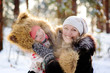 mother and little girl laughing in winter forest