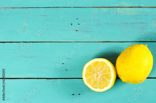 Freshly cut half and whole lemons on rustic boards.