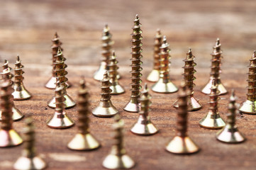 Golden screws on a wooden surface