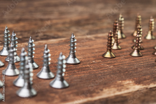 Little golden and silver screws on wood