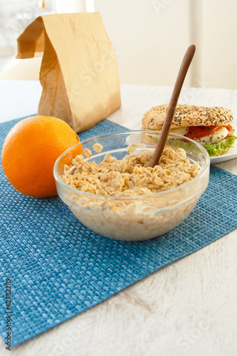 Breakfast with oatmeal, an orange and a sandwich
