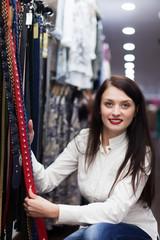 Woman choosing belt at shop