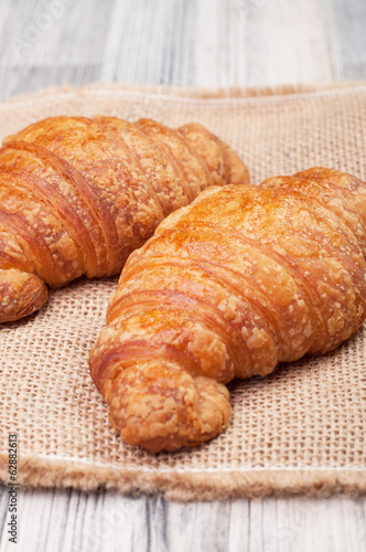 Two croissants on a tablecloth