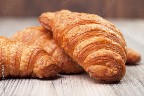 Several croissants on a wooden surface
