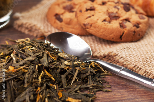 Tea leaves on the foreground and cookies on the background