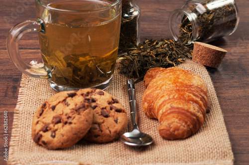 A cup of leaf tea with cookies and a croissant
