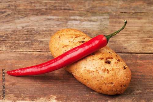 A chilli pepper on the top of a loaf of bread
