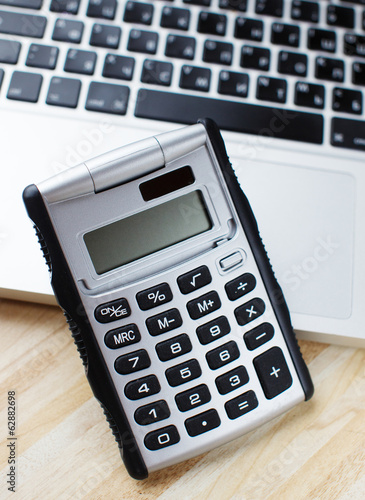 Calculator and a makbook on the background