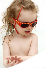 Funny toddler with sunglasses in the bath