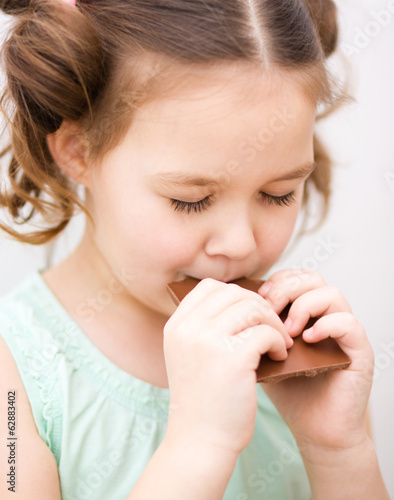 Cute girl is eating chocolate candy