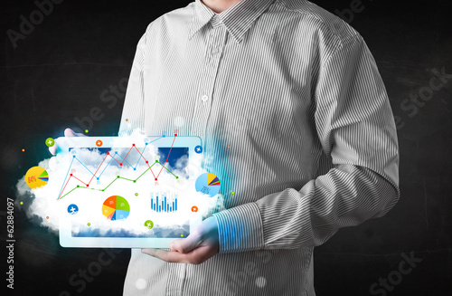 Person holding a touchpad with cloud technology and charts