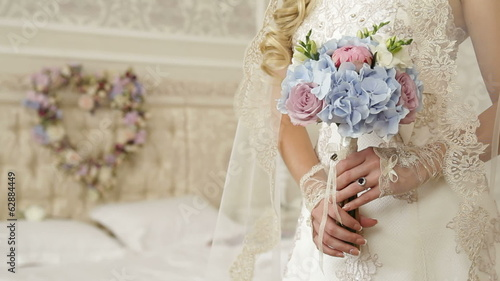 wedding bouquet in bride hands against background heart
