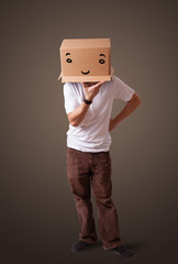 Young man gesturing with a cardboard box on his head with smiley