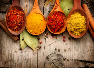 Spices and herbs. Curry, saffron, turmeric, cinnamon over wood